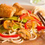 catfish stir fry with noodles, veggies and chopsticks