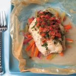 catfish papillote on bed of vegetables and topped with tomatoes