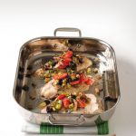 mediterranean catfish topped with olives and tomatoes in baking pan