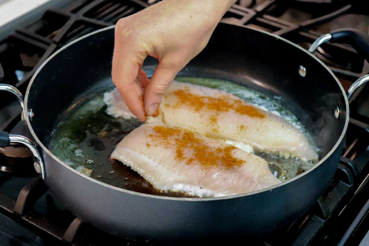 Catfish fillets being seasoned in cast iron skillet