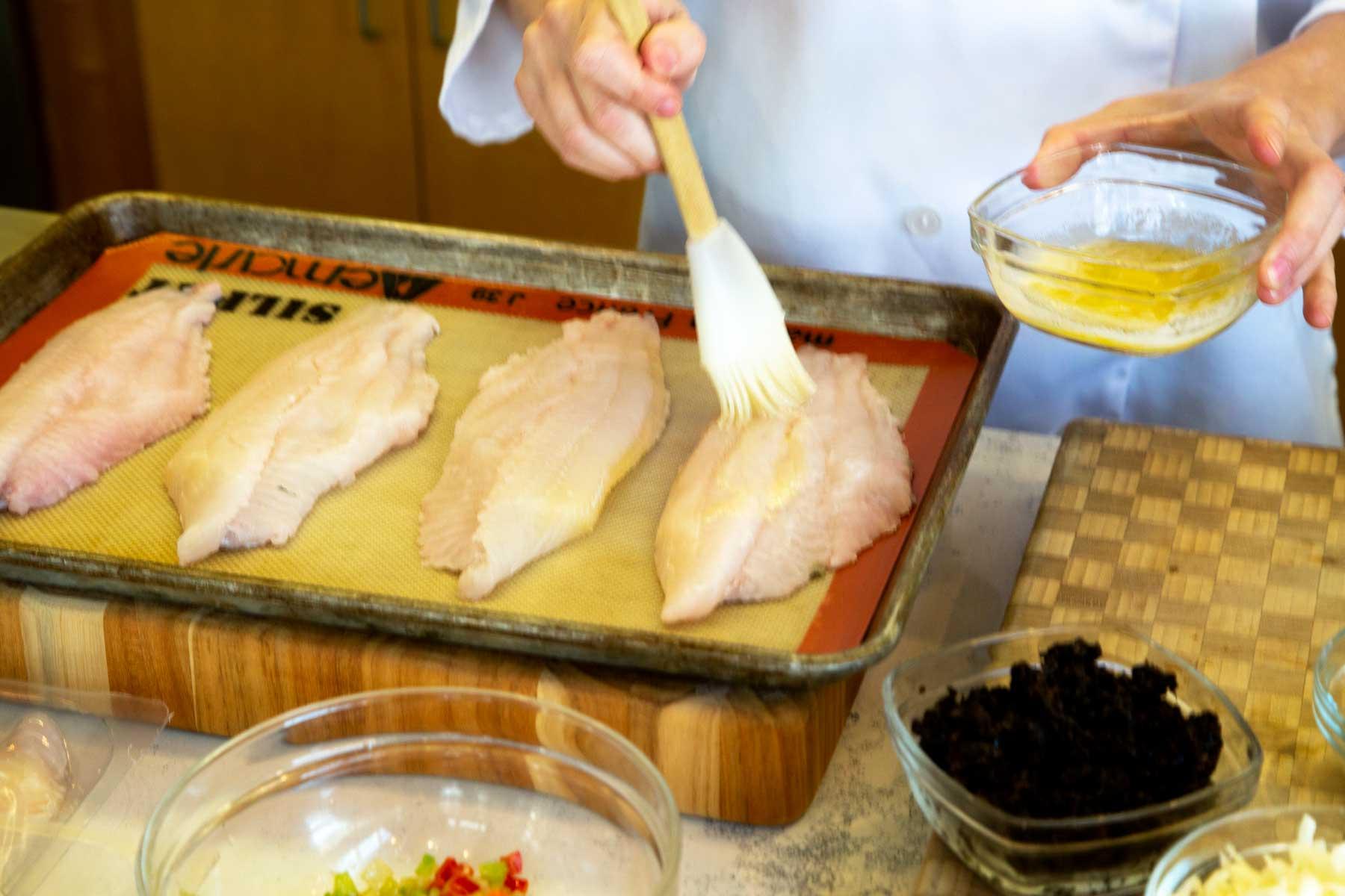 Brushing butter onto catfish fillets on baking sheet