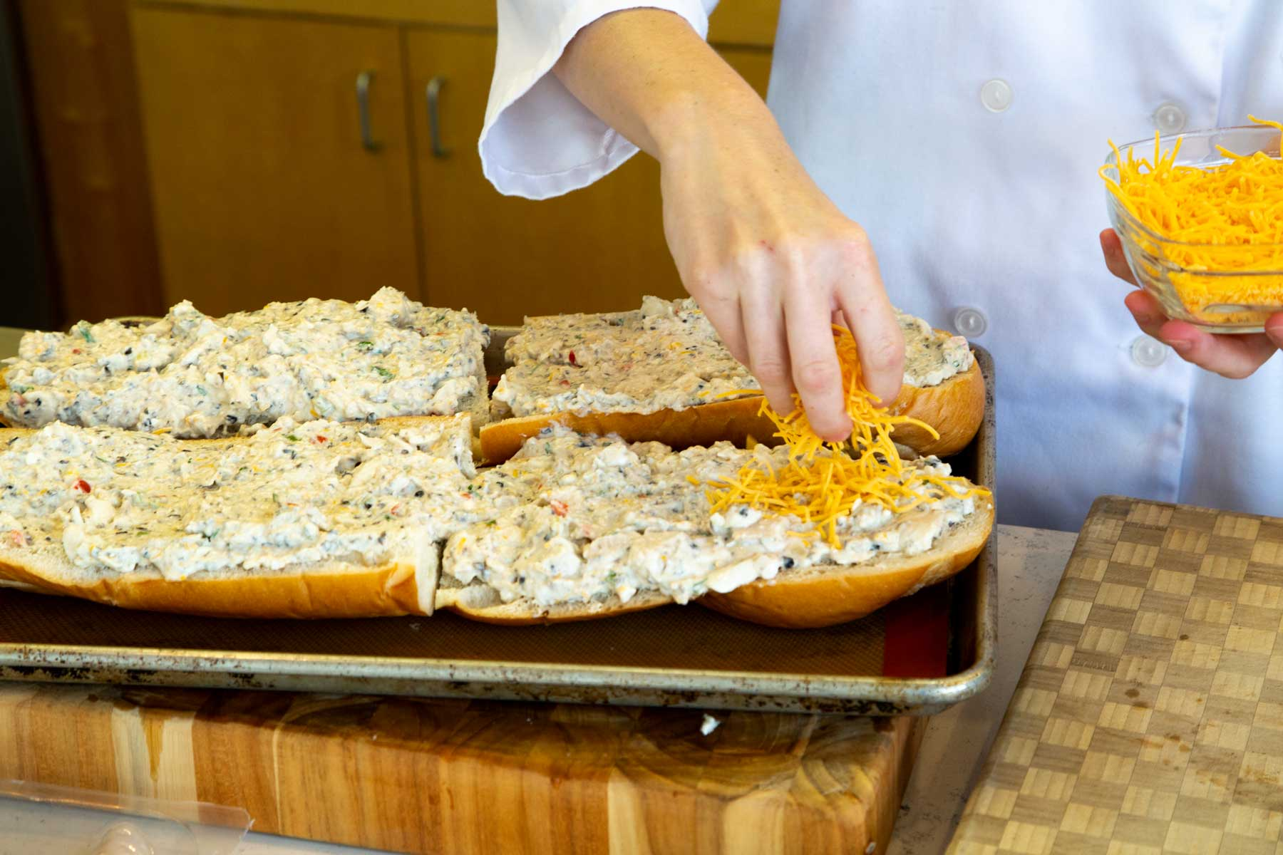 Catfish spread on french bread, sprinkling cheddar cheese on top