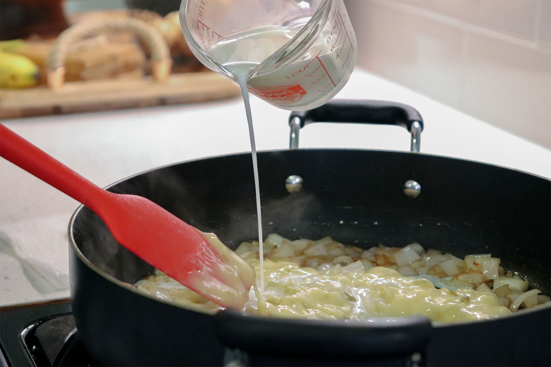 Adding milk to ingredients in cast iron skillet