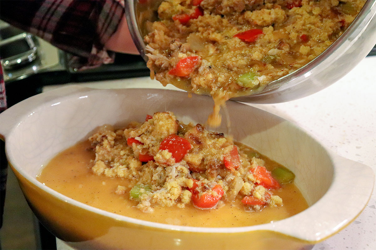 mixed cornbread dressing pouring into baking pan