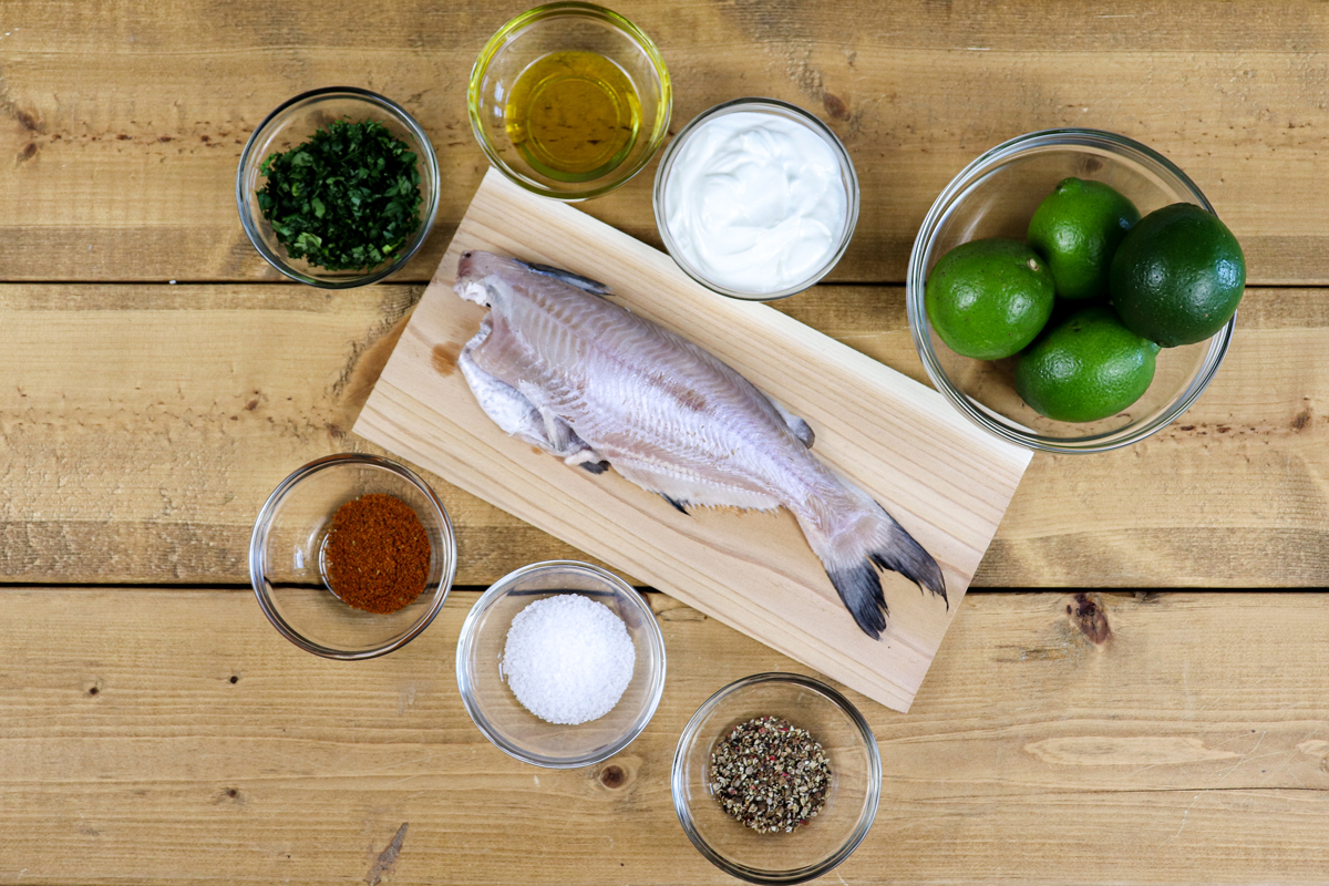 Grilled catfish ingredients including whole fish, spices and limes