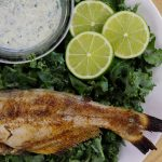 whole grilled catfish with seasoning and sauce on a bed of greens