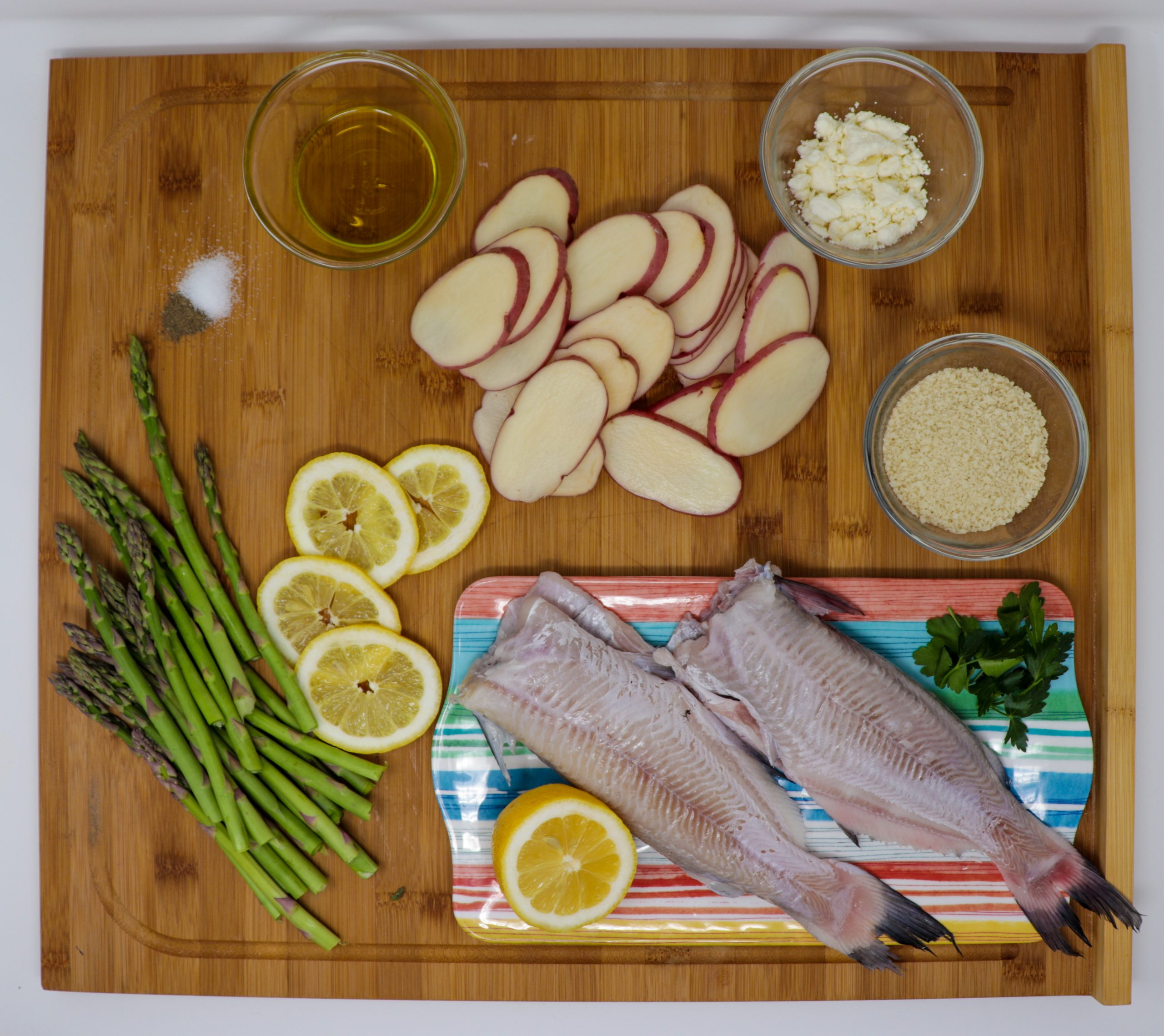Baked catfish ingredients including whole fish, red potatoes, lemons, asparagus and garlic