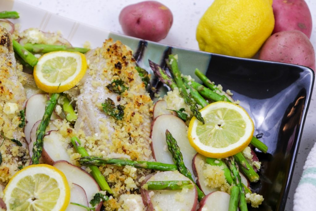 Baked catfish with red potatoes and asparagus on plate