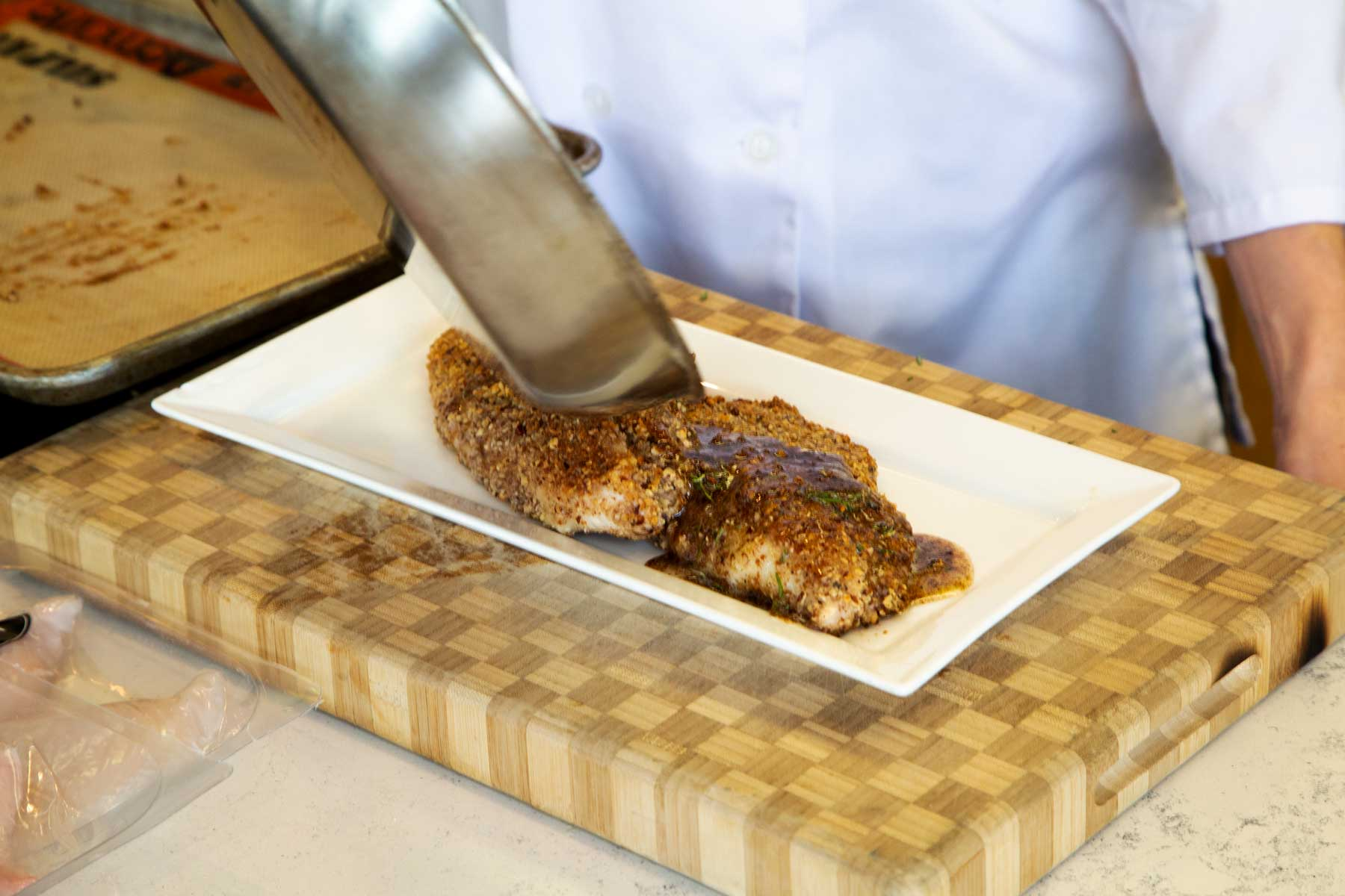 Pouring Sauce over Pecan Crusted Catfish