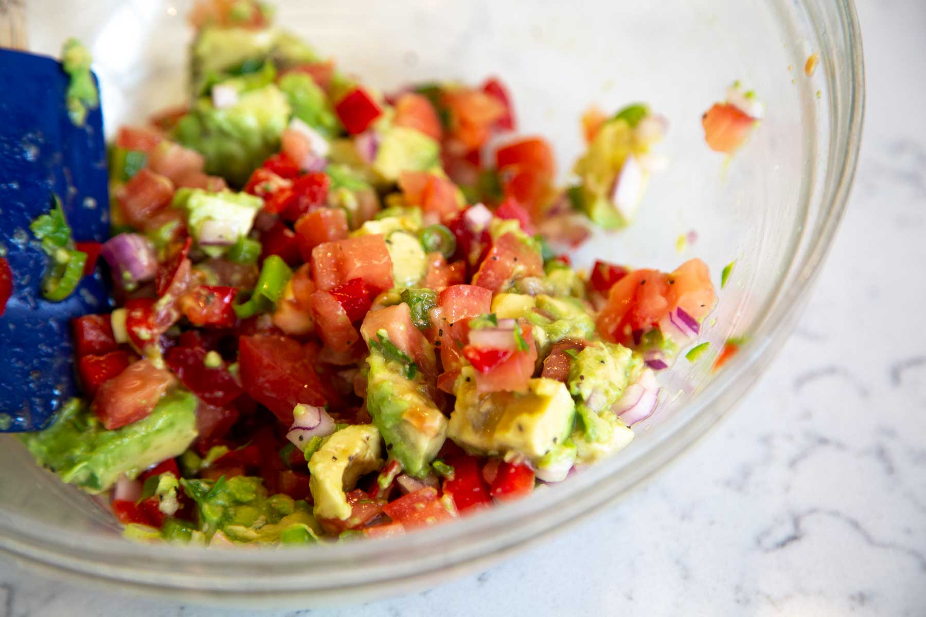 Fresh avocado, tomato, onion and other ingredients in a bowl