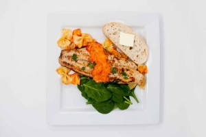 Pan fried catfish with roasted red pepper sauce, spinach and bread on plate