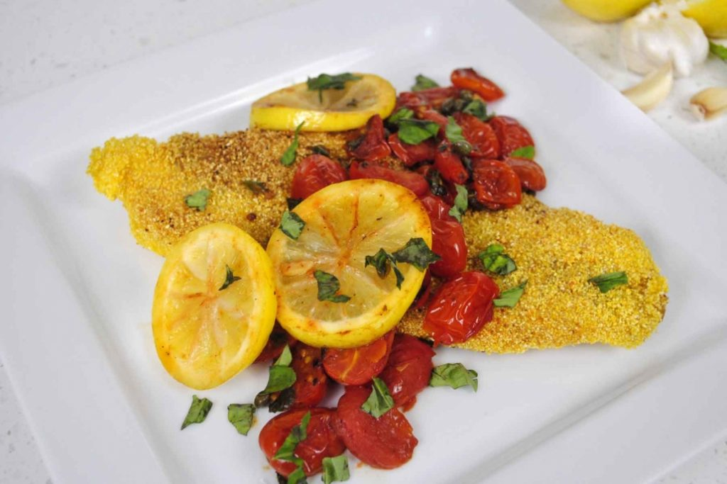 Grits Crusted Catfish topped with tomatoes and lemon