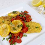 Grits Crusted Catfish topped with tomatoes and lemons