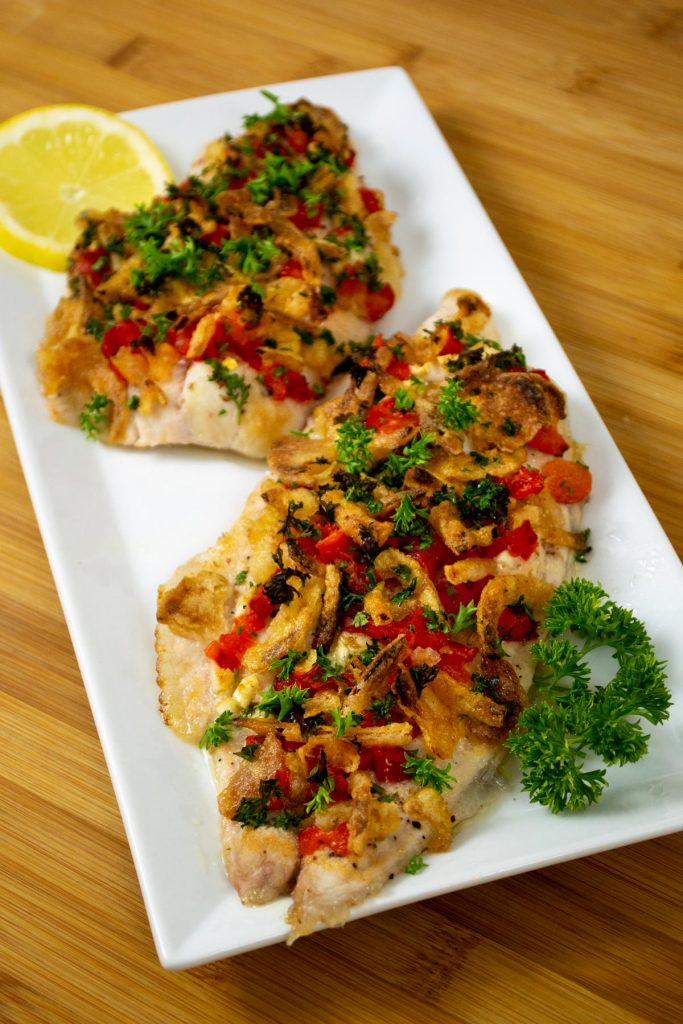 roasted catfish fillets with fresh toppings on plate