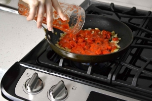 Pouring tomato sauce in skillet