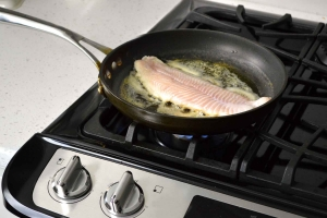 catfish sauteeing in butter on stove