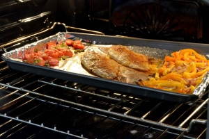 catfish fillets and veggies roasting in oven