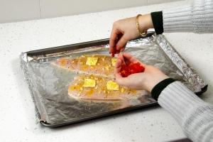 seasoning catfish on baking sheet