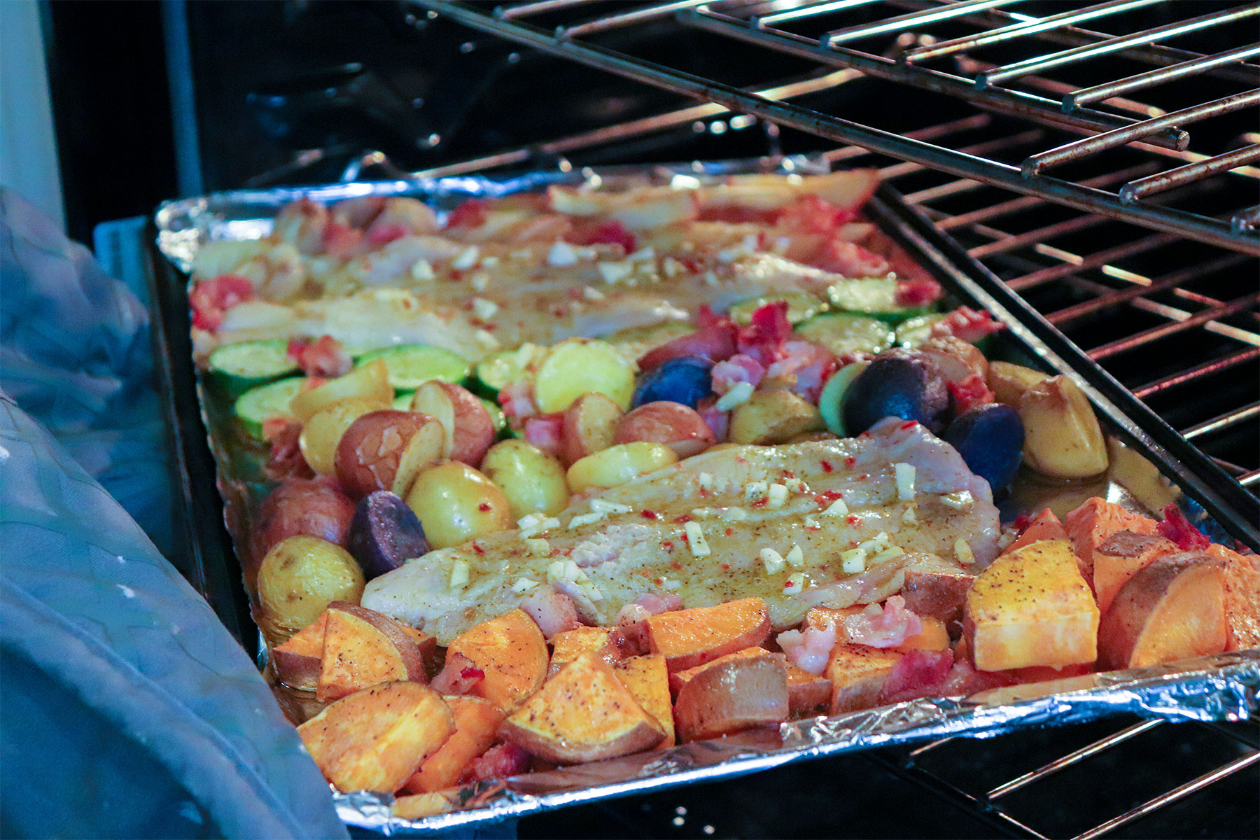 catfish added to sheet pan with veggies in oven