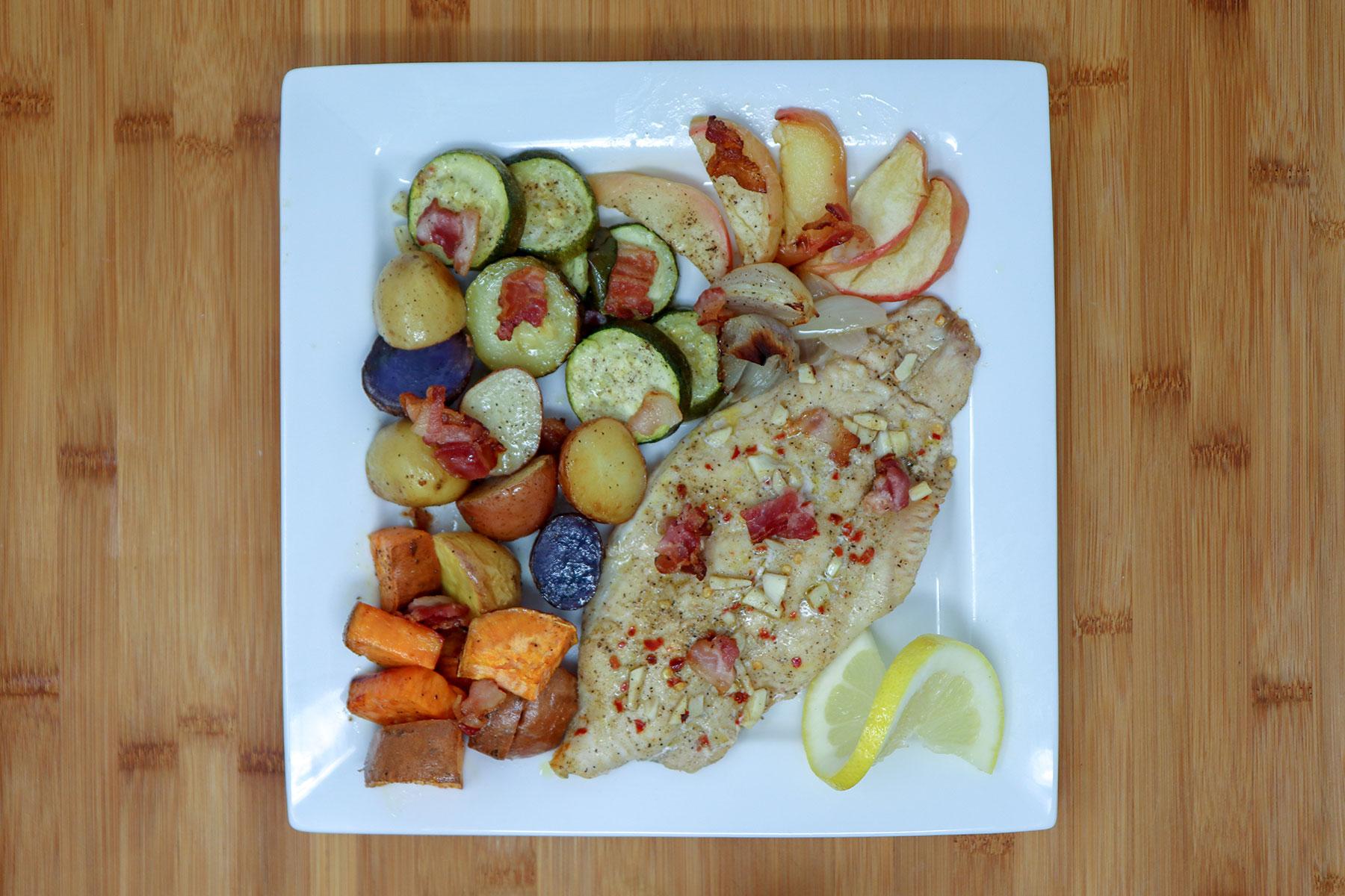 finished sheet pan catfish and veggies on plate