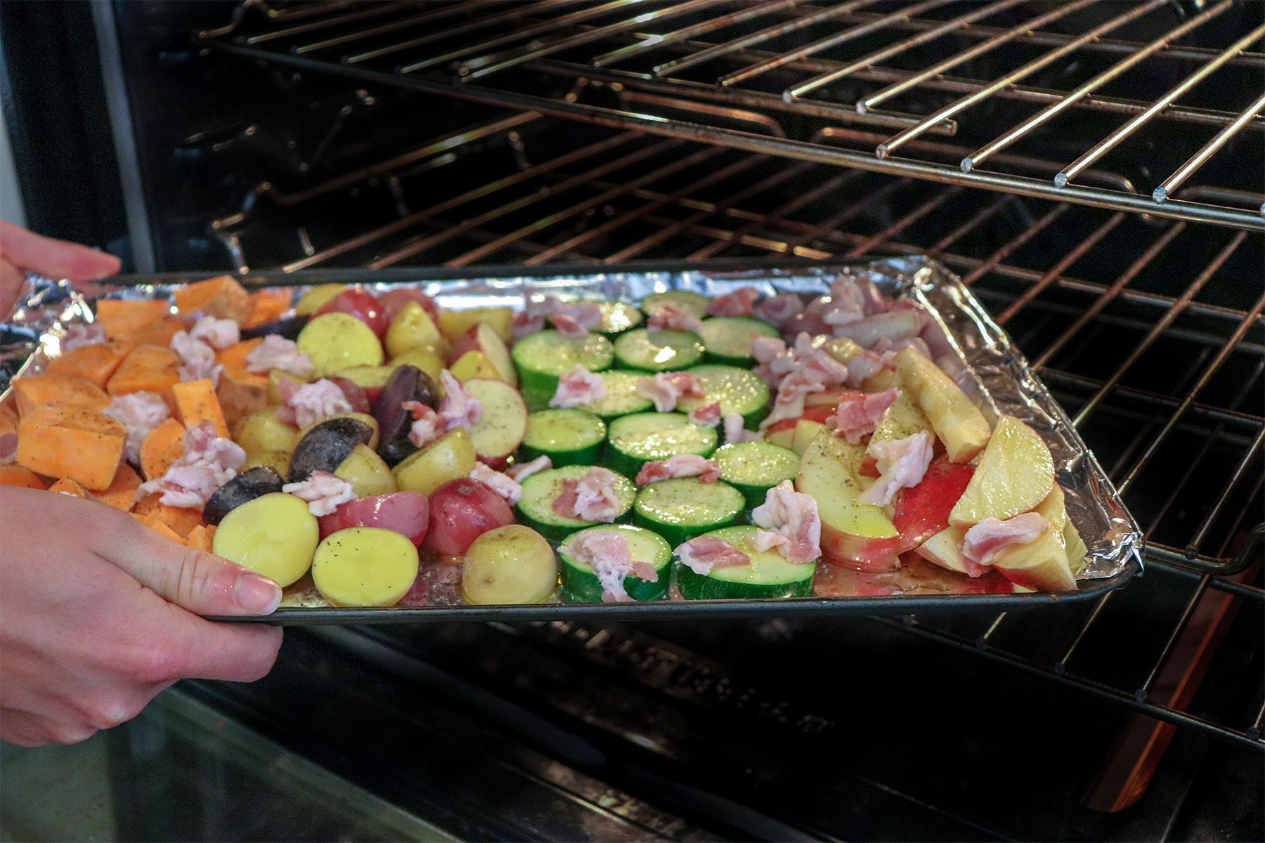sheet pan with veggies and bacon put into oven