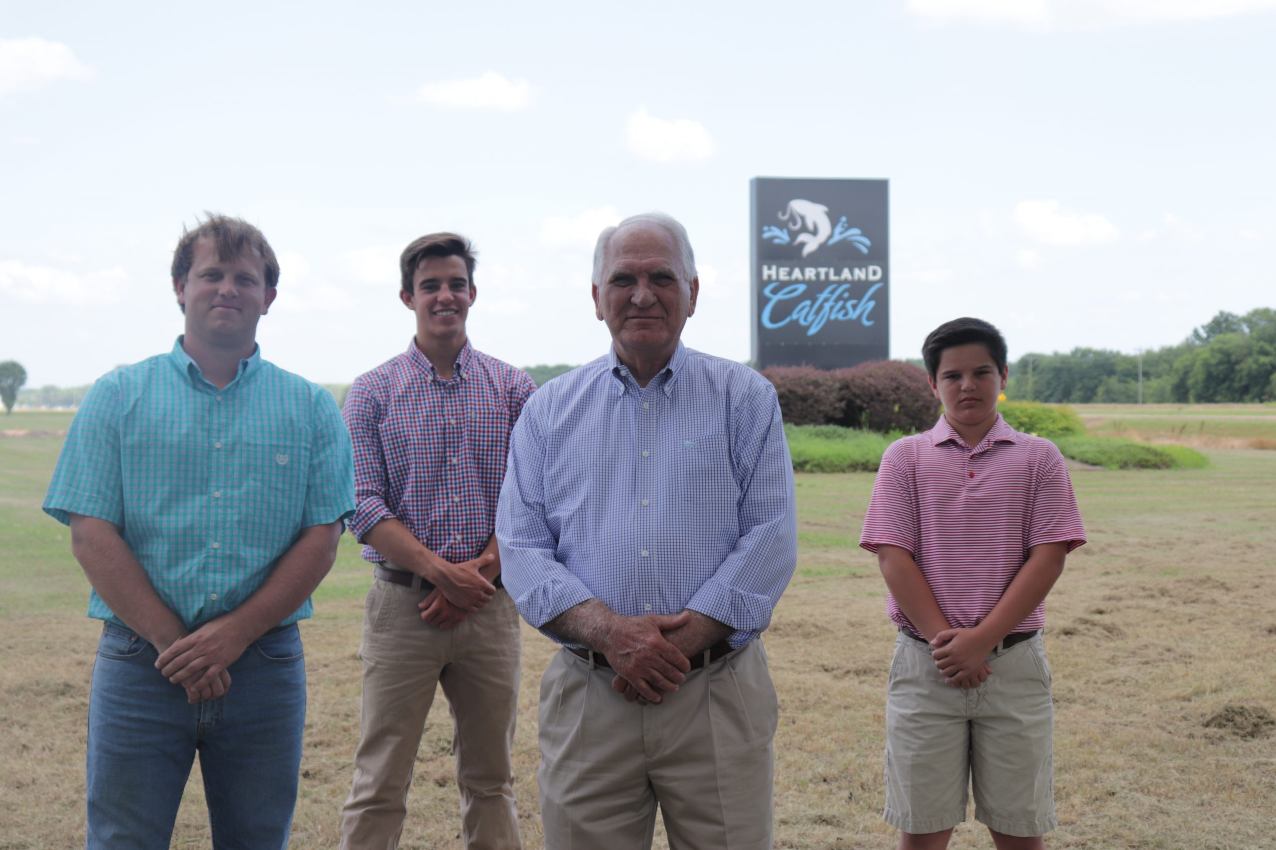 Four generations of Tackett family standing in front of Heartland Catfish sign